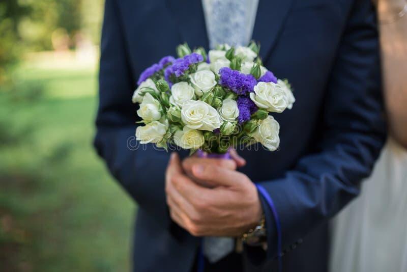 Ramalhete do casamento da posse do noivo à disposição foto de stock