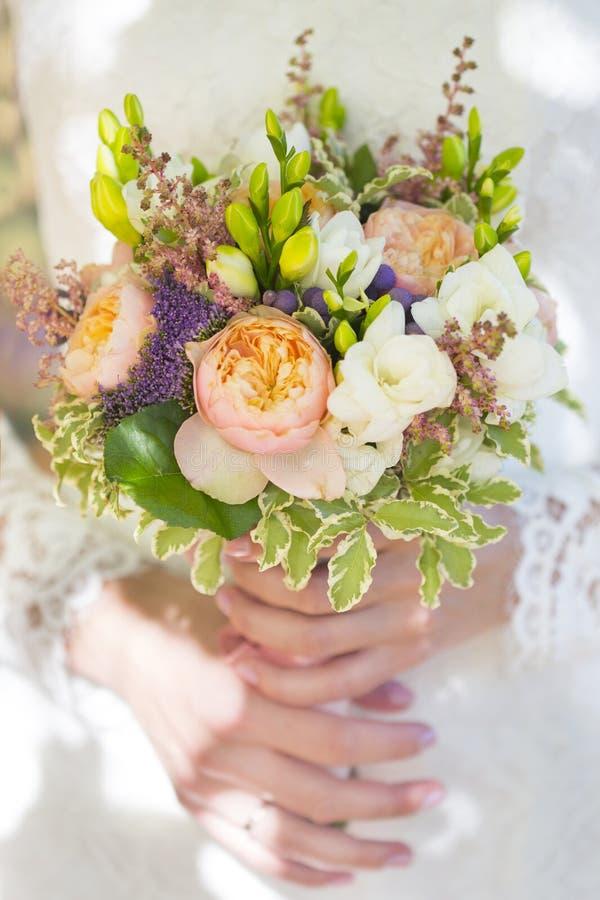 Ramalhete do casamento das flores brancas, violetas e cor-de-rosa nas mãos da noiva fotografia de stock royalty free