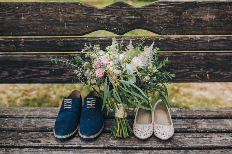 Ramalhete do casamento das flores e das hortaliças e dos noivos das sapatas que encontram-se em um banco de madeira velho imagens de stock