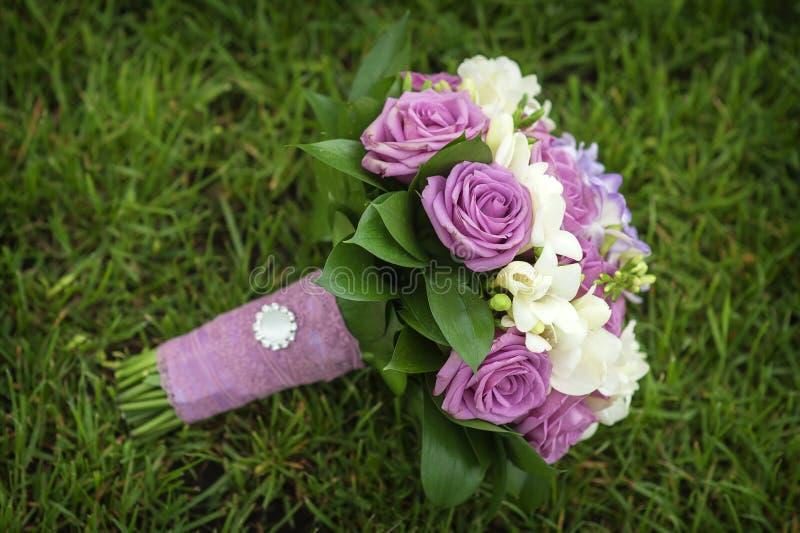 Ramalhete do casamento das flores que encontram-se na grama verde imagens de stock