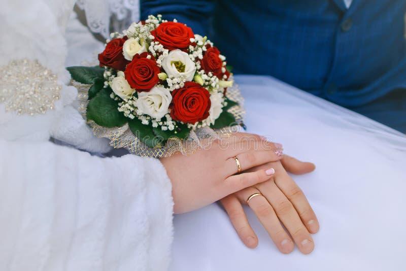 Ramalhete do casamento nas mãos da noiva e do noivo fotos de stock royalty free