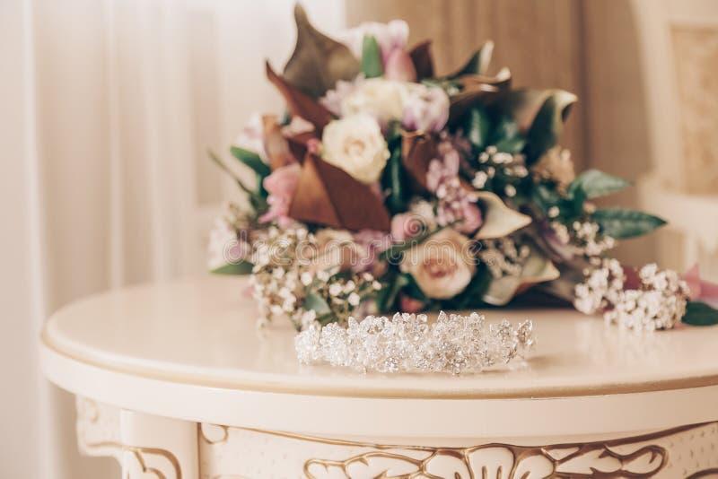 Ramalhete do casamento que encontra-se na tabela coroa da joia no primeiro plano fotografia de stock royalty free