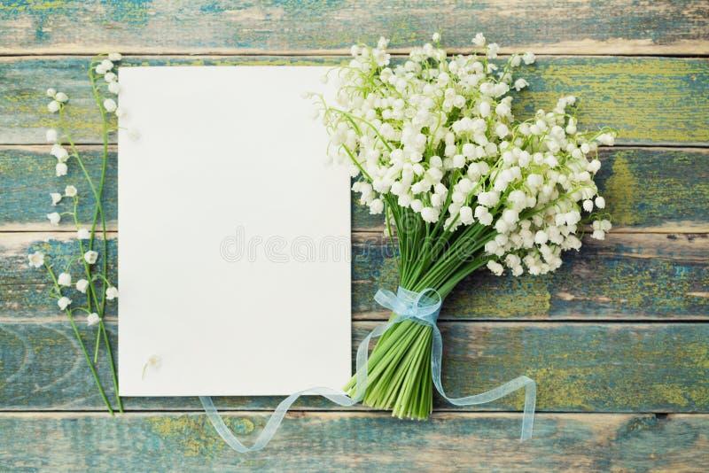 Ramalhete do lírio das flores do vale e da folha de papel vazia na tabela rústica de cima de, cartão bonito do vintage, vista sup foto de stock