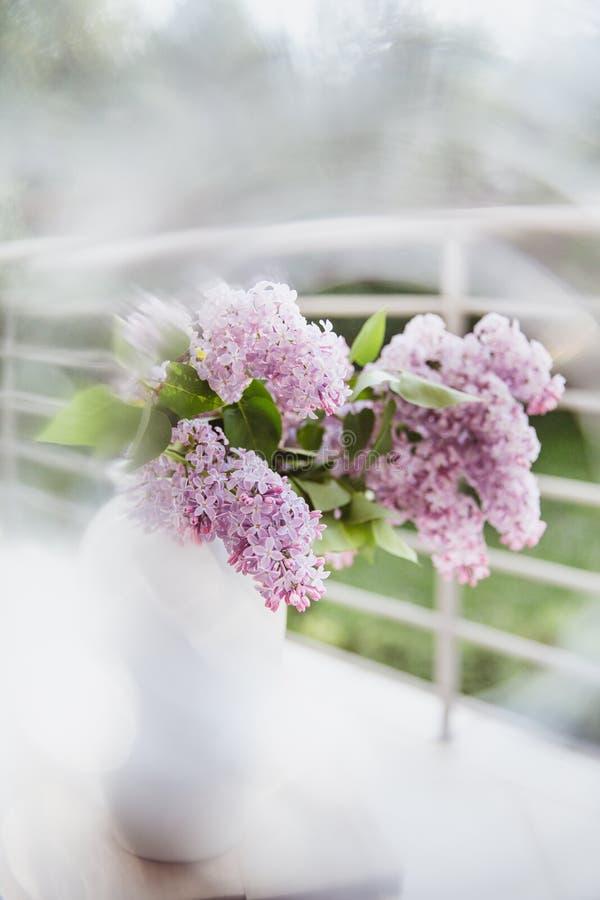 Ramalhete do lilás em um vaso branco em uma tabela de madeira nos raios do sol r imagens de stock
