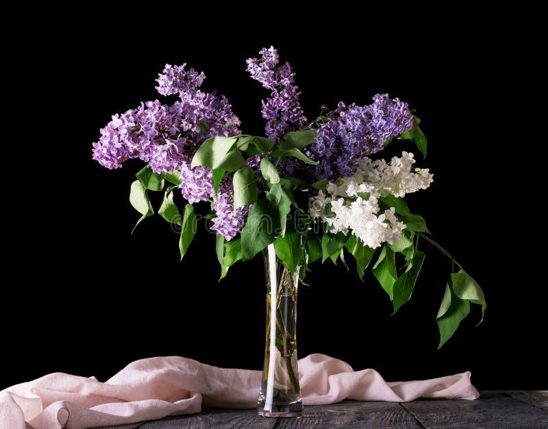 Ramalhete do lilás no vaso de vidro original, ao lado da tela, isolada no preto imagens de stock