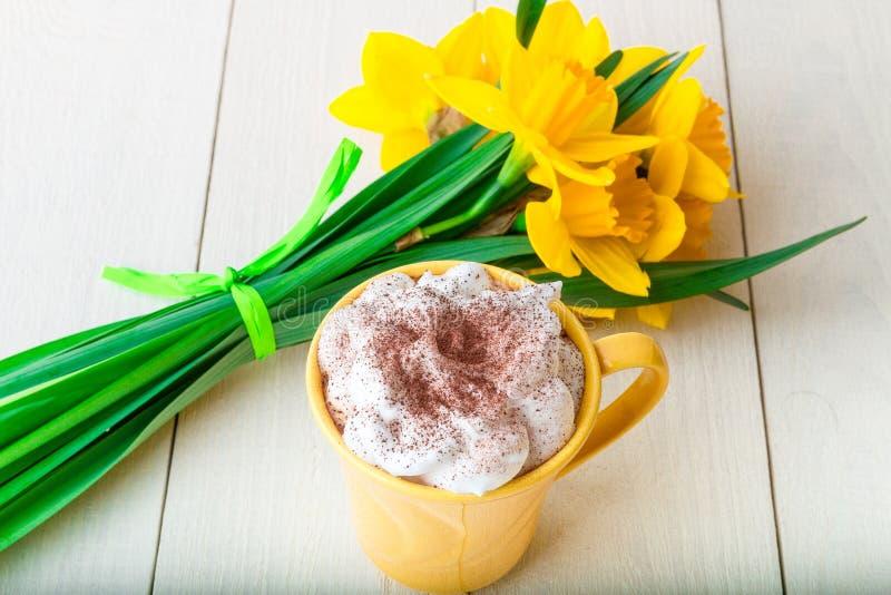 Ramalhete do narciso amarelo perto da xícara de café no fundo de madeira branco Vista superior fotografia de stock royalty free