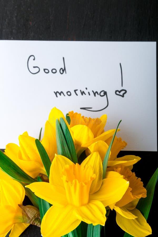 Ramalhete do narciso amarelo perto do cartão com bom dia no fundo preto Vista superior Copie o espaço Dia de mães ou dia das mulh fotografia de stock royalty free