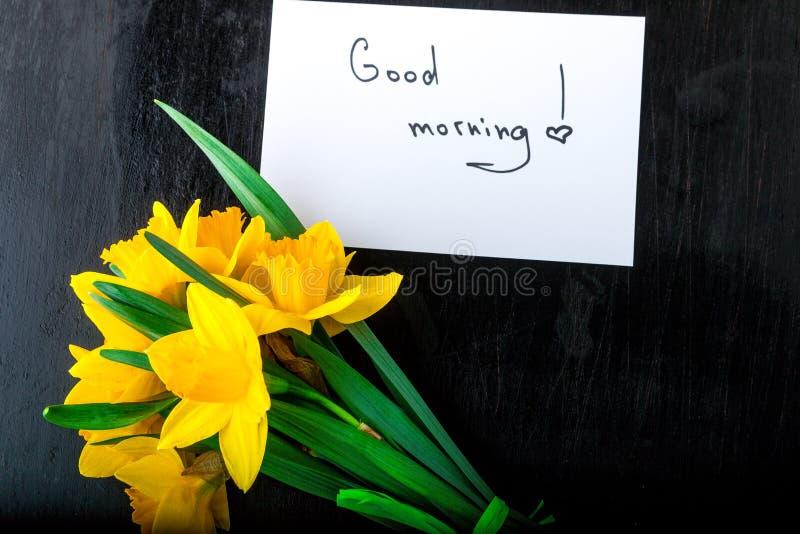 Ramalhete do narciso amarelo perto do cartão com bom dia no fundo preto Vista superior Copie o espaço Dia de mães ou dia das mulh imagem de stock