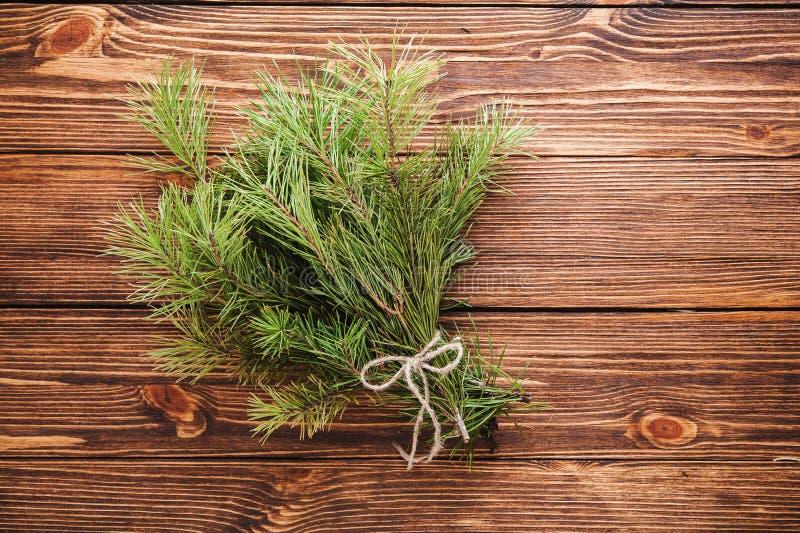 Ramalhete do Natal do ramo de árvore do abeto no fundo de madeira fotografia de stock royalty free