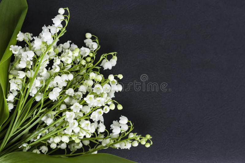 Ramalhete dos lírios brancos do vale em um fundo escuro com uma cópia do espaço fotos de stock