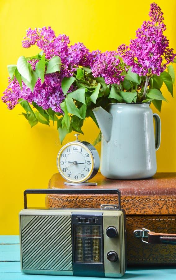 Ramalhete dos lilás na chaleira esmaltada na mala de viagem antiga, rádio do vintage, despertador no fundo amarelo Do estilo vida imagem de stock royalty free