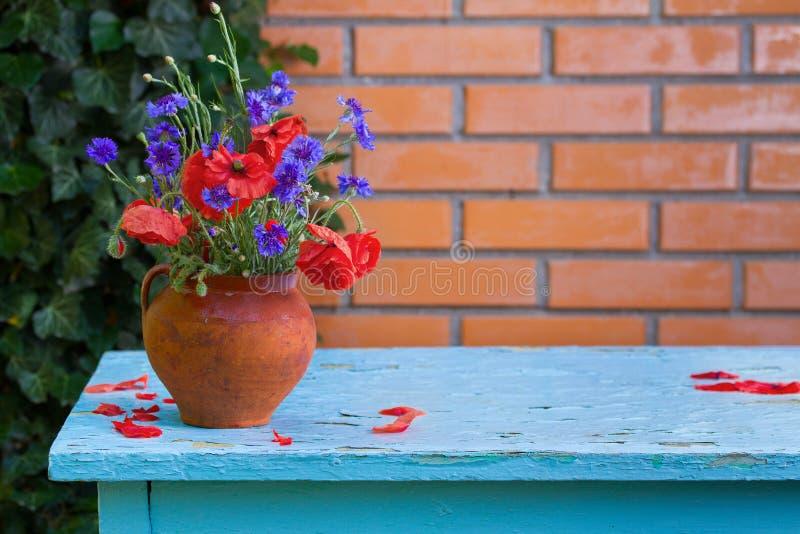 Ramalhete dos wildflowers - centáureas e papoilas no vaso na tabela ao lado do fundo da parede de tijolo no jardim fotografia de stock