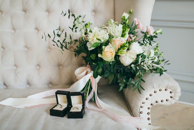 Ramalhete e anéis rústicos do casamento na caixa negra em um sofá luxuoso dentro artwork imagem de stock royalty free