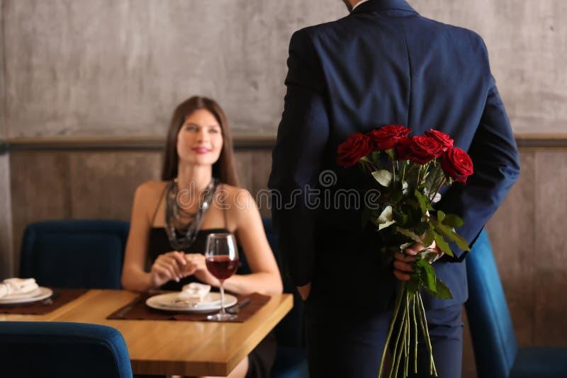 Ramalhete escondendo do homem de rosas bonitas para sua amiga atrás da parte traseira no restaurante fotografia de stock
