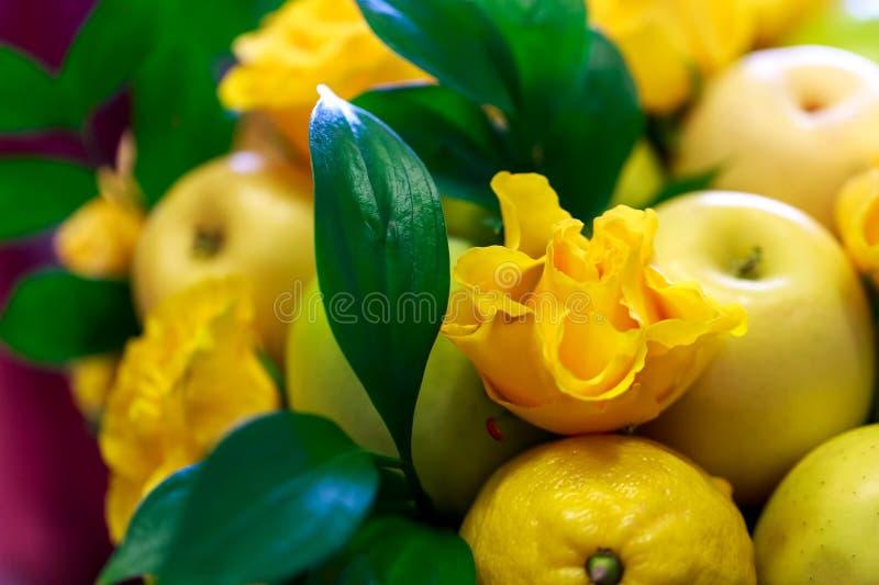 Ramalhete feito a mão bonito que consiste em maçãs amarelas e verdes, em limões, em folhas do verde e em rosas amarelas imagem de stock royalty free