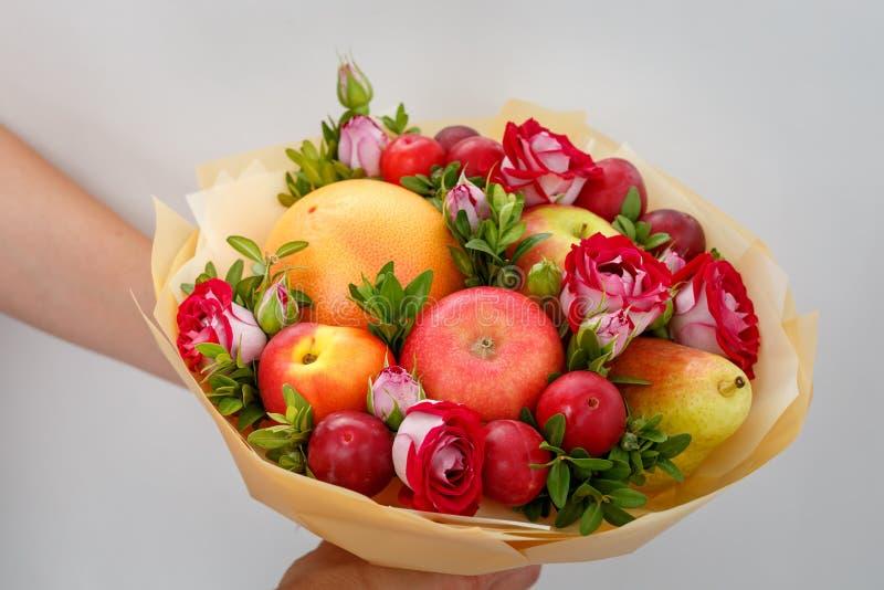 Ramalhete festivo original que consiste em maçãs, em peras, em ameixas, em toranjas e em rosas de florescência nas mãos de uma me imagens de stock royalty free