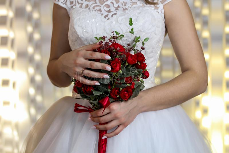 Ramalhete fino do casamento do claretroz nas mãos da noiva fotografia de stock