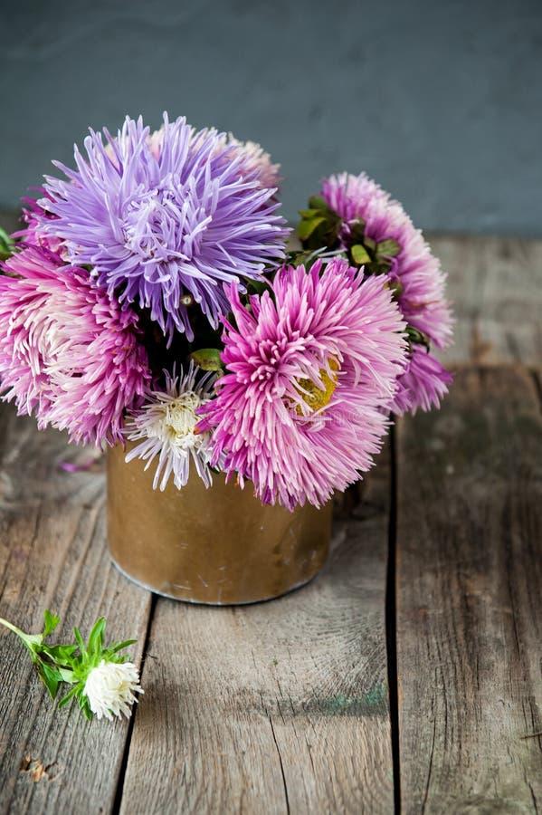 Ramalhete floral da beleza com os ásteres coloridos no potenciômetro retro do metal na tabela de madeira rústica velha Fundo do v fotos de stock royalty free