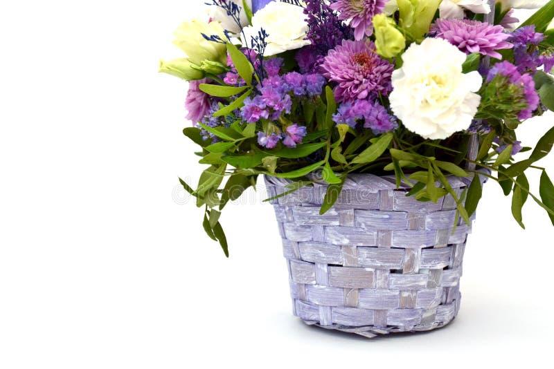 Ramalhete isolado de flores da mola na cesta de madeira de vime decorativa de flores lilás e roxas em um fundo branco fotografia de stock royalty free