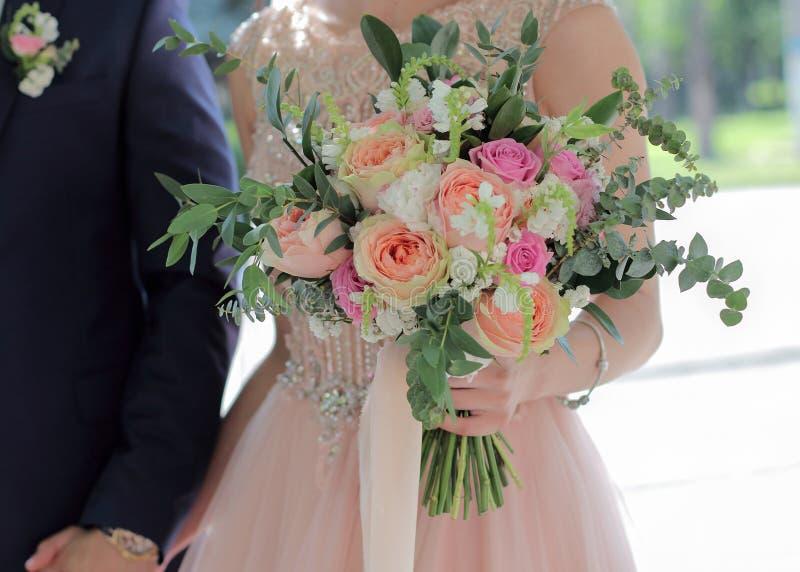 Ramalhete nupcial bonito nas mãos da noiva Ramalhete do casamento de rosas do pêssego por David Austin, aqua da rosa do rosa da ú foto de stock royalty free