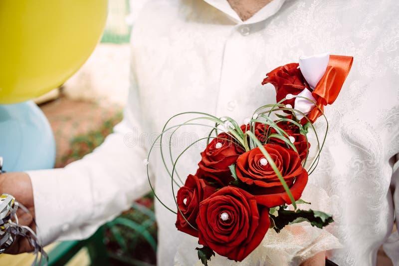 Ramalhete nupcial de rosas vermelhas nas mãos do noivo imagem de stock