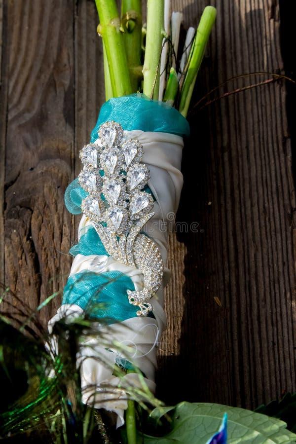 Ramalhete nupcial do casamento do pavão no fundo de madeira fotografia de stock