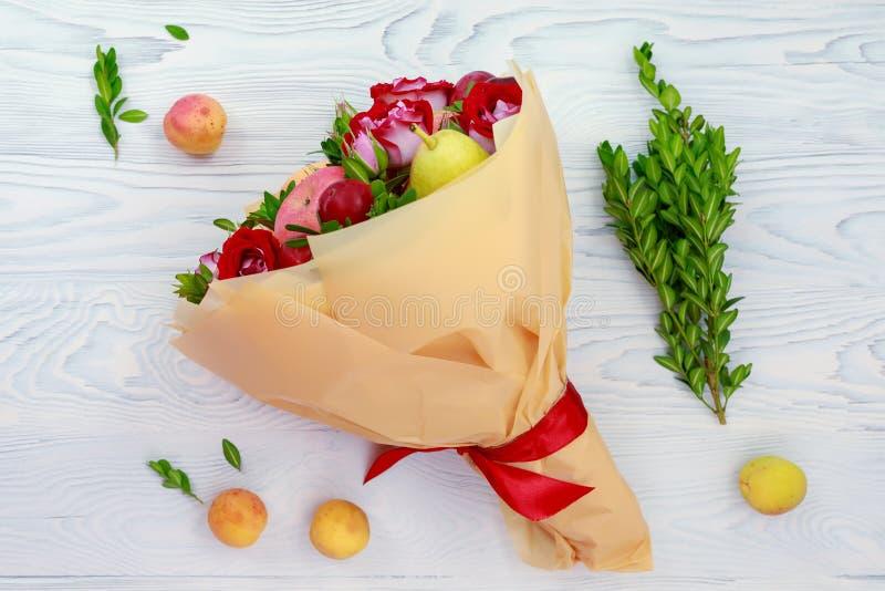 Ramalhete original de mentiras dos frutos e das flores em uma tabela de madeira fotos de stock royalty free