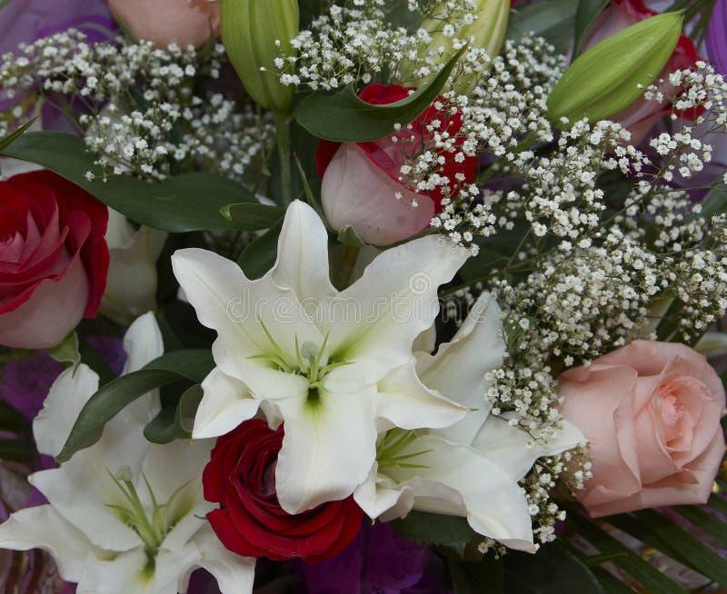 Ramalhete: pique rosas vermelhas e os lírios brancos. imagens de stock royalty free