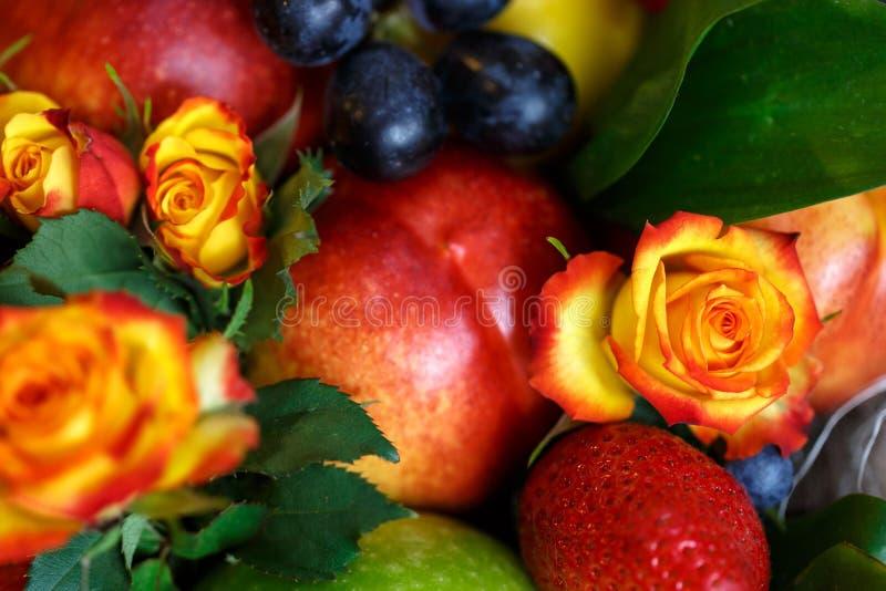 Ramalhete que consiste em maçãs, em laranjas, em morangos, em uvas, em ameixas e em flores do close-up das rosas do jardim foto de stock