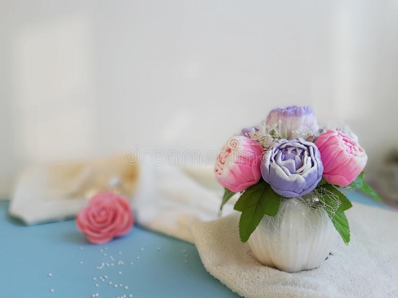 Ramalhetes das peônias na superfície azul de toalha na frente da parede branca fotografia de stock royalty free