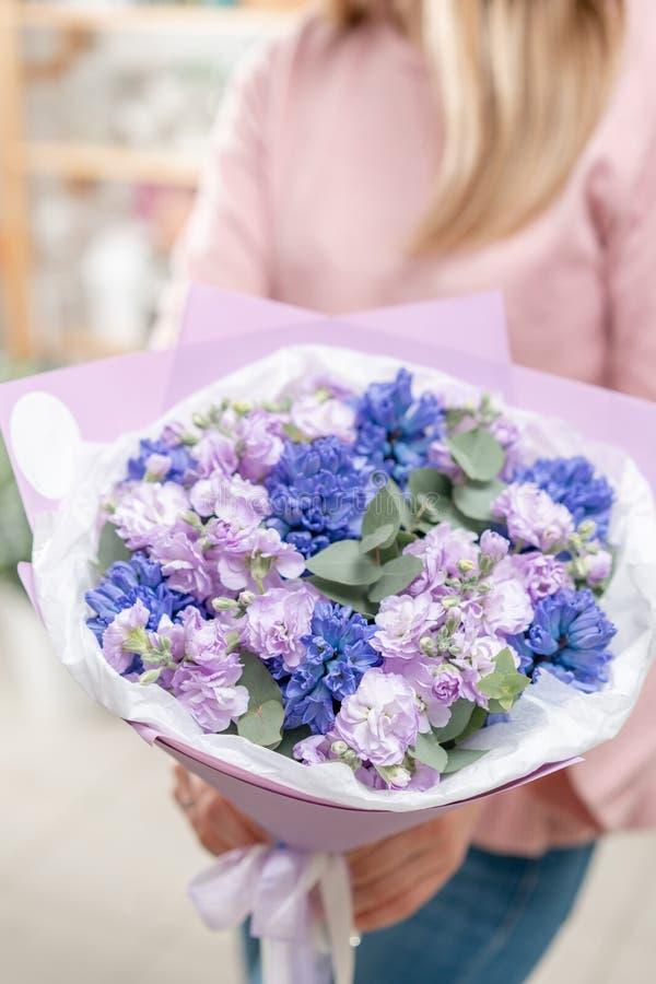 Ramalhetes de jacintos azuis e matthiola da cor lilás na mão da mulher Flores da mola do jardineiro holandês Conceito da fotografia de stock