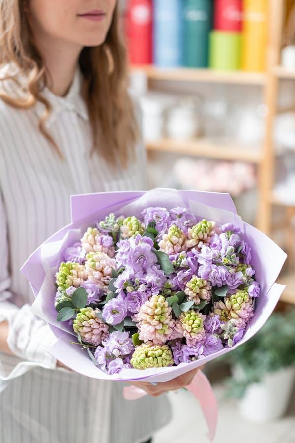 Ramalhetes de jacintos cor-de-rosa e matthiola da cor lilás na mão da mulher Flores da mola do jardineiro holandês Conceito da imagem de stock royalty free