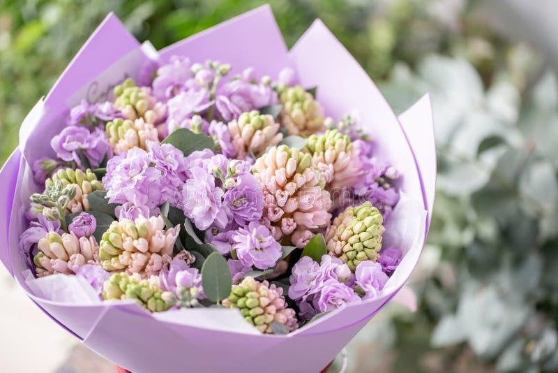 Ramalhetes de jacintos cor-de-rosa e matthiola da cor lilás no vaso na tabela de madeira Flores da mola do jardineiro holandês imagens de stock