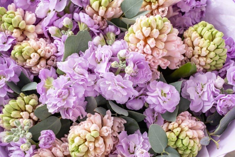 Ramalhetes de jacintos cor-de-rosa e matthiola da cor lilás no vaso na tabela de madeira Flores da mola do jardineiro holandês fotografia de stock royalty free