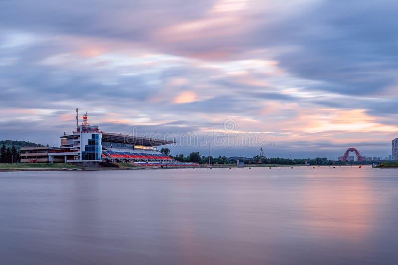 """Ramant le canal """"Krylatskoe """"à l'aube Ciel et nuages sombres à l'aube Tribune des fans Endroit de sports photos libres de droits"""