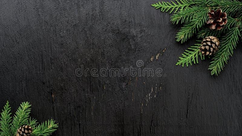 Ramas de árbol de abeto de la Navidad y conos del pino en un tablero de madera negro foto de archivo libre de regalías