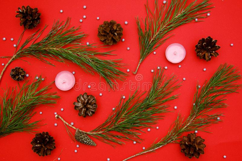 Ramas de árbol de navidad con los conos en un fondo rojo fotografía de archivo