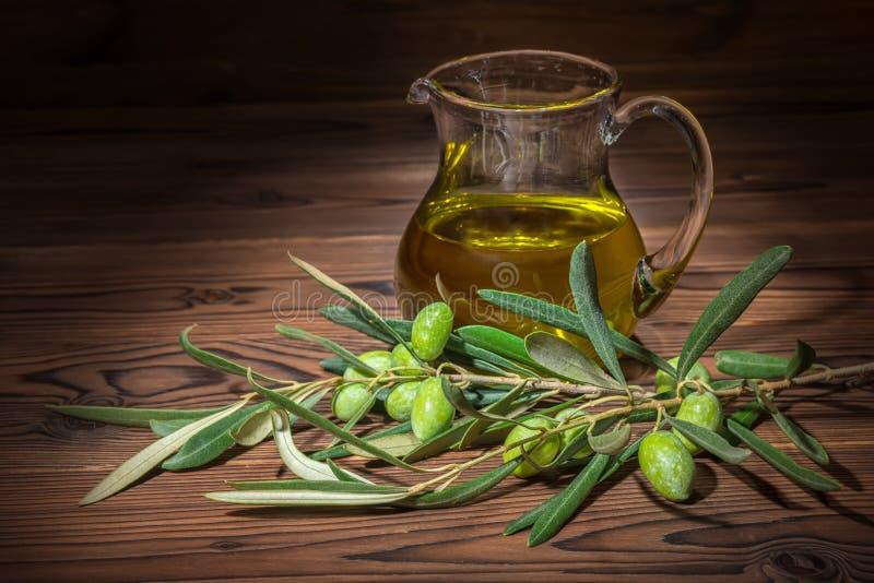 Ramas verdes del olivo con las bayas y el aceite fresco en woode foto de archivo libre de regalías