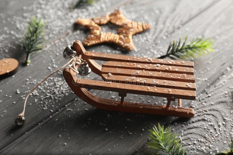Ramas y trineo de árbol de navidad en fondo de madera fotografía de archivo libre de regalías