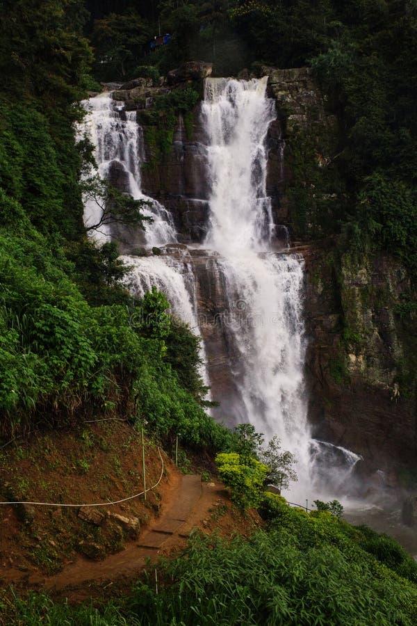 Ramboda Falls with green plantation around stock photography