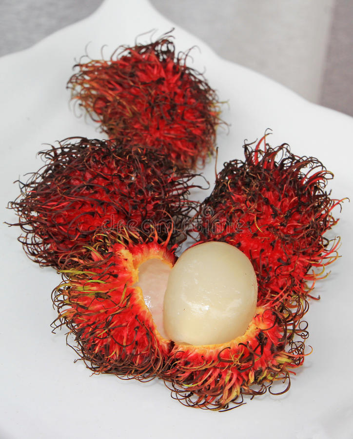 Rambutan Fruit. Pieces of rambutan fruits on a white serving dish, one displaying the meat of this exotic Southeast Asian exotic red hairy fruit stock image