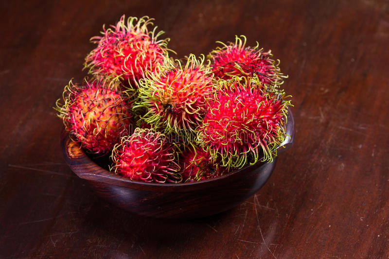 Rambutan a sweet tropical fruit. Wooden bowl filled with rambutan placed on a wooden table, Rambutan is a sweet tropical fruit royalty free stock photography