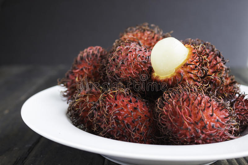 Rambutan. Is a tropical sweet and sour, white, translucent fruit with a red leathery skin with hairy protuberances stock image