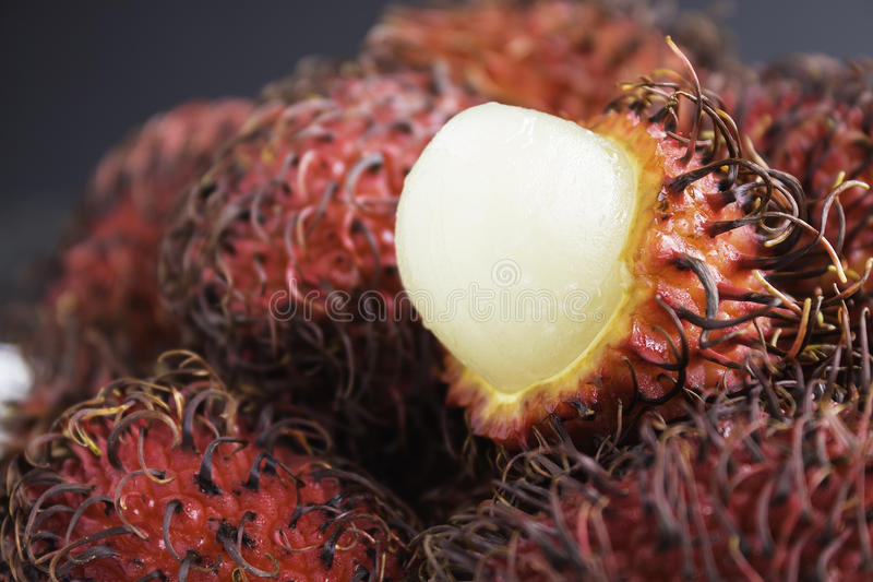 Rambutan. Is a tropical sweet and sour, white, translucent fruit with a red leathery skin with hairy protuberances royalty free stock images