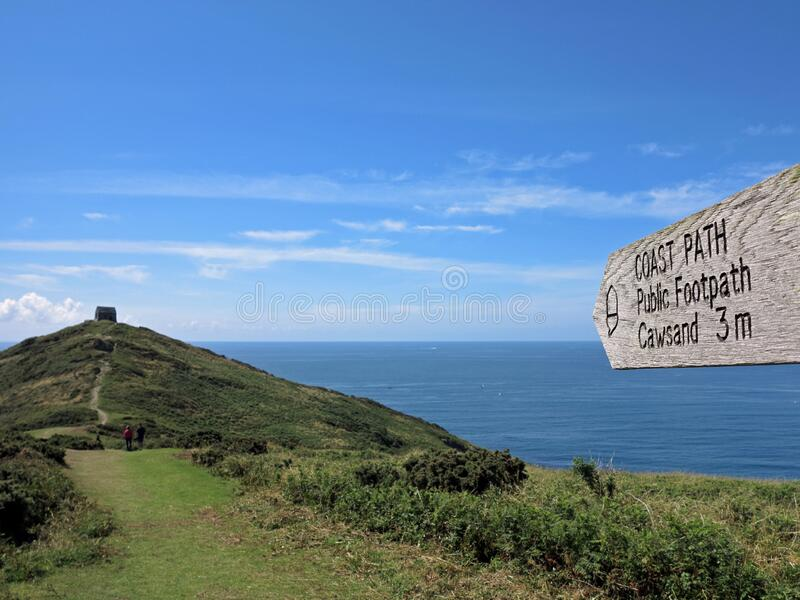 Rame head coastpath, Cornwall England. With St Micheal`s church. Wodden finger post on grass path pointing towards a derelict church on the Rame peninsula royalty free stock images