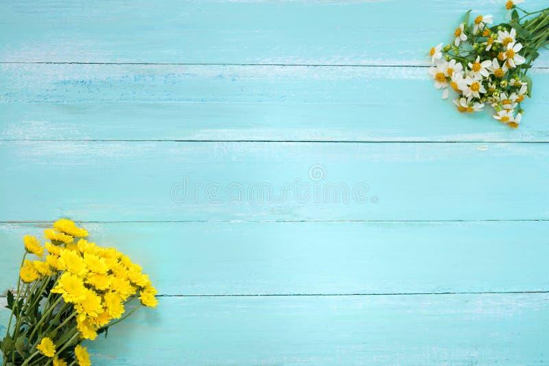 Rame machte von den weißen wilden Blumen und von den gelben Chrysanthemenblumen auf blauem hölzernem Hintergrund stockfoto