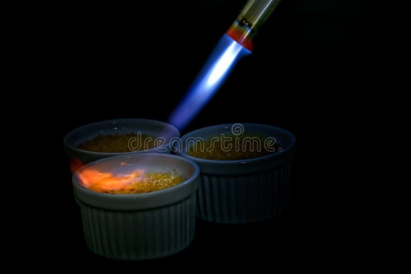 Ramekin caramelizing de la lámpara de soldar de la nata quemado Aislado en bla fotografía de archivo libre de regalías