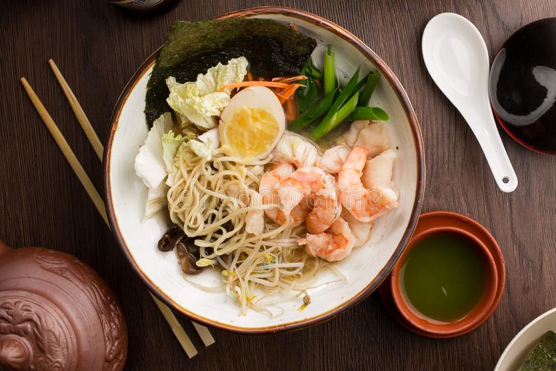 Ramen asiáticos con los camarones y los tallarines en un restaurante fotos de archivo
