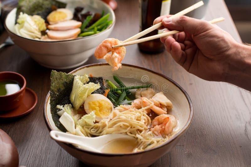 Ramen asiatico mangiatore di uomini con i gamberetti e le tagliatelle in un ristorante fotografia stock