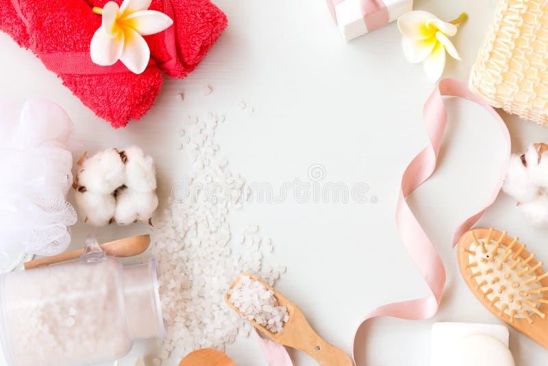 Ramen av brunnsorttemat anmärker på vit bakgrund Salt för bad, hårkam, rosa handdukar och bomullsblomma med kopieringsutrymme arkivfoton